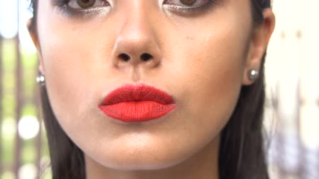 sensuous : Outdoors shot closeup face of beautiful young woman with red lips looking into the camera, blowing kiss and smiling - video in slow motion