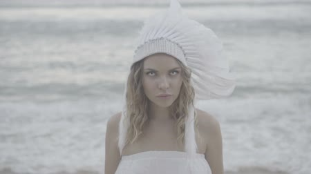 wampir : Closeup portrait of blond woman wearing white eye lenses and indian feather hat looking at the camera while standing at the beach over beautiful sea and sky background