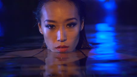 deslumbrante : Closeup face of sexy beautiful woman with wet hair looking into the camera while relaxing in the swimming pool and during summer evening over blue lights background - video in slow motion