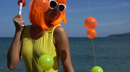 peruca : Closeup of sexy beautiful woman in modern futuristic style posing with coloured balls attached to umbrella during sunny summer day over blue sea and sky background. Creative look of woman wearing yellow swimsuit, orange wig and white sunglasses