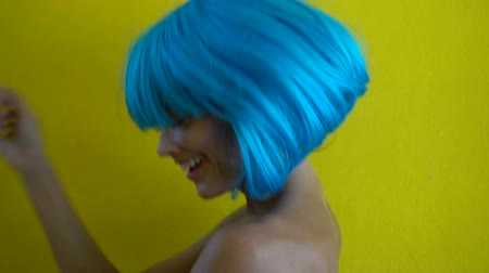 serseri : Side view closeup portrait of sexy beautiful woman with colourful makeup in modern futuristic style smiling and dancing over yellow wall background. Creative look of woman wearing blue bikini and wig - slow motion video