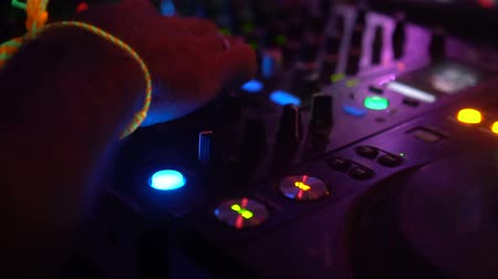 dengeleme : Closeup of DJ hands playing music set on mixer and mixing console at the party