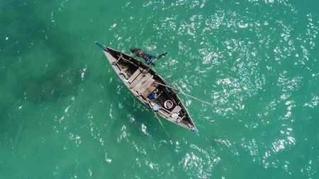 высота над уровнем моря : Aerial top view of boat on the sea and fisherman in the water hunting