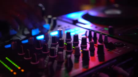dengeleme : Closeup of DJ hands playing music set on mixer and mixing console at the party - video in slow motion
