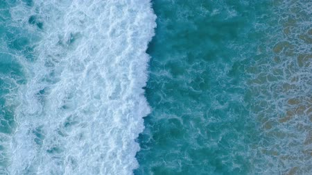 tiro : Aerial drone slow motion video of beautiful sea waves crashing on shore. Tracking shot of ocean waves creating a texture from the white sea foam