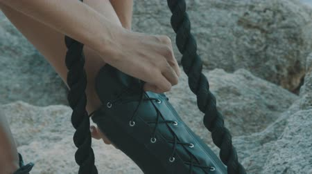 camurça : Closeup of woman hands tying and adjusting shoelaces outdoor - video in slow motion