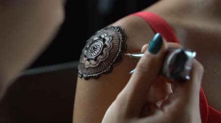 gravura : Closeup video of henna tattoo artist draws on womans shoulder - video in slow motion Vídeos