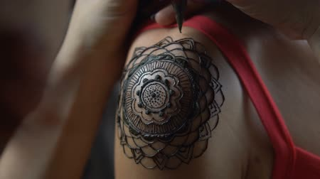 rytina : Closeup video of henna tattoo artist draws on womans shoulder - video in slow motion Dostupné videozáznamy