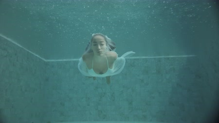 underwater video : Beautiful woman in white bikini with long hair swimming underwater with see-trough fabric. Fairy tale mermaid magic world concept - video in slow motion Stock Footage