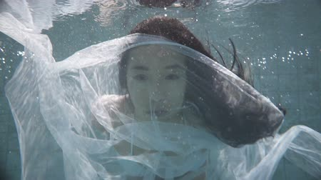 gerçeküstü : Closeup of beautiful woman in white bikini with long hair swimming underwater with see-trough fabric on her face. Fairy tale mermaid magic world concept - video in slow motion Stok Video