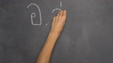 conversa : Womans hand writing Thai letter with white chalk on blackboard
