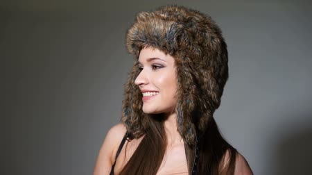 high spirited : Closeup portrait of pretty young brunette woman in fur hat with her hands to the ear flaps smiling at the camera