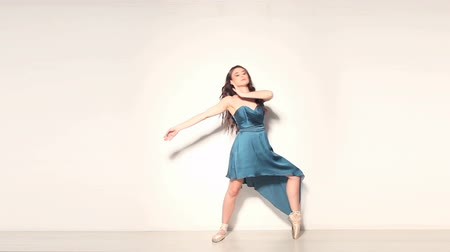 balerína : Young and beautiful brunette ballerina in blue dress dancing over white background Dostupné videozáznamy