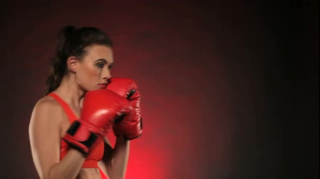 bokszoló : Side view of beautiful woman boxer wearing red gloves throwing punches and smiling isolated over dark background Stock mozgókép