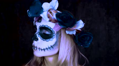 florido : Closeup face of woman with Mexican sugar skull makeup and flowery wreath looking into the camera. Creative, artistic, Halloween concept Stock Footage