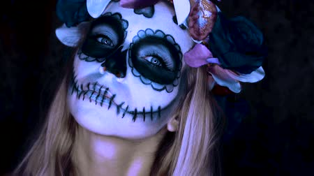 сахар : Closeup face of woman with Mexican sugar skull makeup and flowery wreath looking into the camera. Creative, artistic, Halloween concept Стоковые видеозаписи