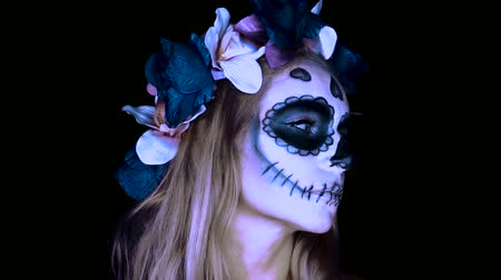 florido : Closeup face of woman with Mexican sugar skull makeup and flowery wreath looking into the camera. Creative, artistic, Halloween concept - slow motion video