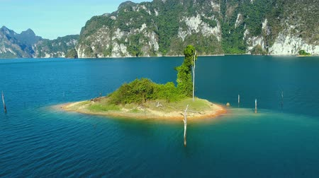 surat : Aerial drone view of small rock on the lake in Khao Sok National Park, Surat Thani, Thailand Stock Footage