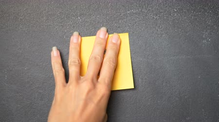 conversa : Closeup womans hand sticking note with letter O on the blackboard - video in slow motion