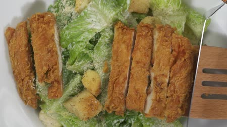 césar : Top view closeup shot putting catted breaded chicken on the salad - video in slow motion