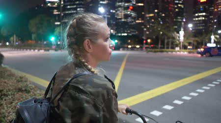 night singapore : Attractive happy woman enjoying a bike ride through the city at night Stock Footage
