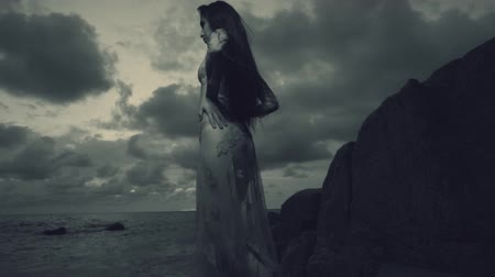 меланхолия : Beautiful mysterious woman in long dress at the sandy beach near rocks over sea and cloudy sunset sky background - black and white video in slow motion Стоковые видеозаписи