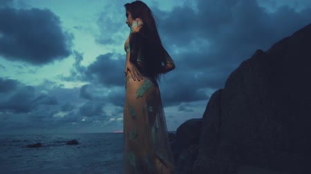 bohyně : Beautiful mysterious woman in long dress at the sandy beach near rocks over sea and cloudy sunset sky background - video in slow motion Dostupné videozáznamy