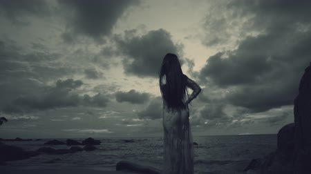 ninfa : Back view of beautiful mysterious woman in long dress at the sandy beach near rocks over sea and cloudy sunset sky background - black and white video in slow motion
