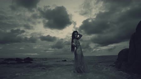 ninfa : Beautiful mysterious woman in long dress at the sandy beach near rocks over sea and cloudy sunset sky background - black and white video in slow motion Vídeos
