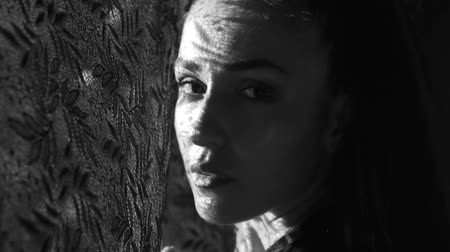 ümitsizlik : Beautiful woman looking through the window, she has got lace curtain pattern shadow and sun rays on her face - black and white video in slow motion