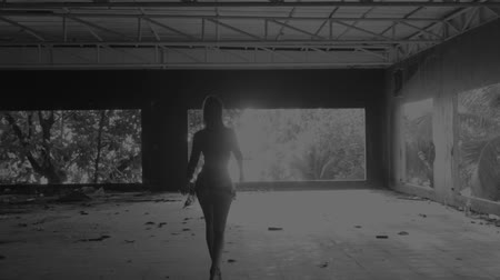 sentir : Back view of beautiful woman walking down in abandoned building - white and black video in slow motion
