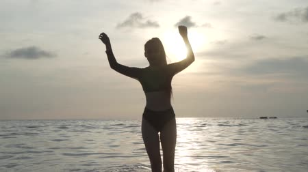 sedutor : Beautiful woman in black swimwear enjoying her holiday on the beach during sunset - video in slow motion