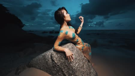 bohyně : Beautiful mysterious woman in long dress relaxing on the rock at the sandy beach over sea and cloudy sunset sky background