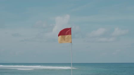 rescuer : Red and yellow warning flag on the stormy beach over blue ocean and cloudy sky background Stock Footage