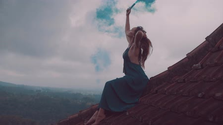 sky bomb : Beautiful woman in long dress sitting with blue colored smoke on tiled red roof of the house against amazing mountain view and cloudy sky background - video in slow motion