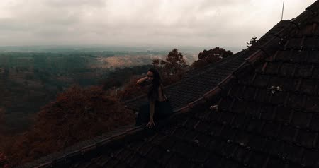 posando : Aerial drone view of beautiful woman in long blue dress sitting on tiled red roof of the house against amazing mountain view and cloudy sky background - video in slow motion