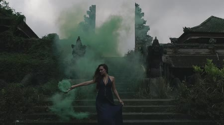 чувственный : Beautiful woman with colored smoke on the outdoors entrance stairs of abandoned hotel - video in slow motion Стоковые видеозаписи