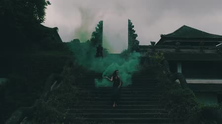 sky bomb : Beautiful woman with colored smoke on the outdoors entrance stairs of abandoned hotel - video in slow motion Stock Footage