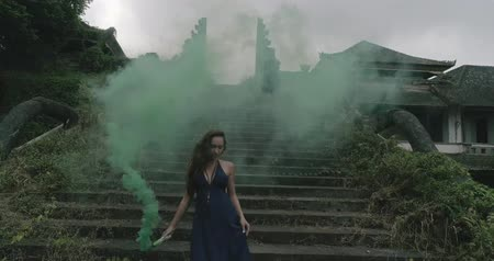 barevný : Beautiful woman with colored smoke on the outdoors entrance stairs of abandoned hotel - video in slow motion Dostupné videozáznamy