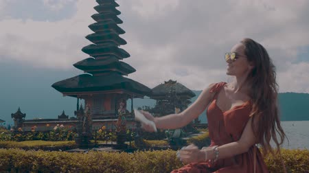 gyümölcsöskert : Young female tourist enjoys her holiday at Ulun Danu Batur temple on the island of Bali, Indonesia - video in slow motion