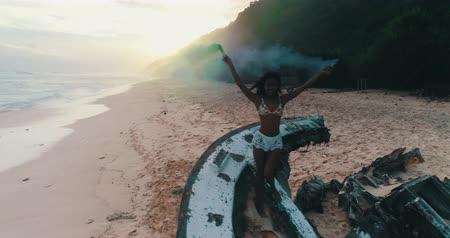 sky bomb : Aerial drone view of beautiful girl with colored smoke standing on the shipwreck at the beach during amazing sunset - video in slow motion Stock Footage