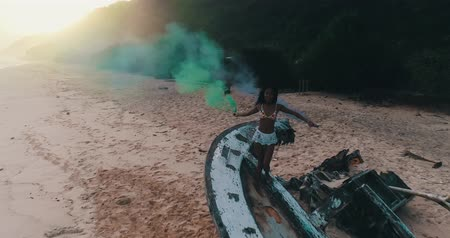 csontváz : Aerial drone view of beautiful girl with colored smoke standing on the shipwreck at the beach during amazing sunset - video in slow motion Stock mozgókép