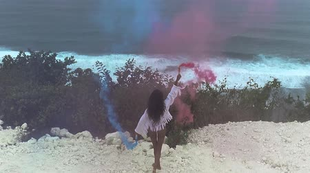zadek : Aerial drone view of beautiful girl with colored smoke playing at the mountain field over ocean and cloudy sky background - video in slow motion