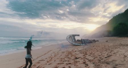 sky bomb : Aerial drone view of beautiful girl playing with colored smoke near the shipwreck at the beach during amazing sunset - video in slow motion