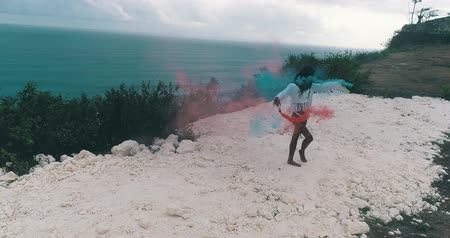 sky bomb : Aerial drone view of beautiful girl with colored smoke playing at the mountain field over ocean and cloudy sky background - video in slow motion