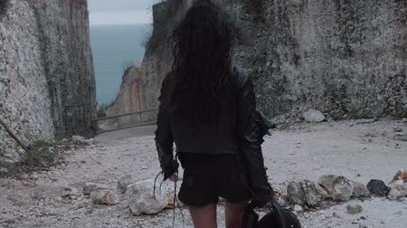 přezka : Back view of beautiful woman motorcycle rider walking with helmet near amazing limestone cliffs - video in slow motion