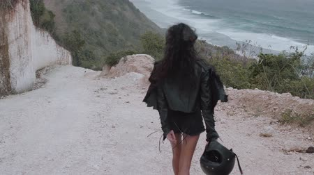 helmets : Back view of beautiful woman motorcycle rider walking with helmet near amazing limestone cliffs over sea  background - video in slow motion Stock Footage