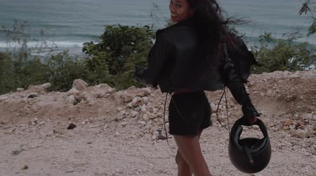 spona : Beautifu happy woman motorcycle rider walking with helmet near amazing limestone cliffs over sea  background - video in slow motion Dostupné videozáznamy
