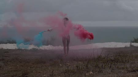 csikk : Back view of beautiful girl with colored smoke running at the mountain field over ocean and cloudy sky background - video in slow motion Stock mozgókép