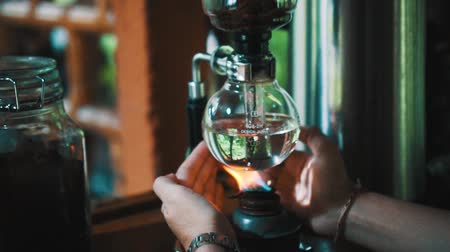 drinking coffee : Female hands covering fire under vacuum with Luwak coffee. Amazing view of alternative coffee maker machine - video in slow motion